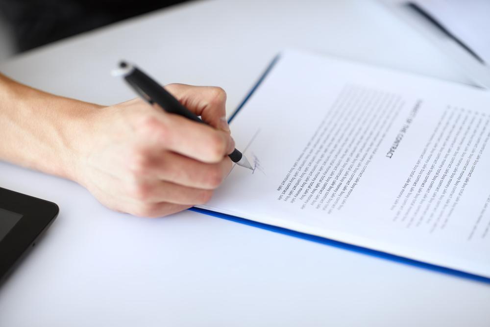Persona firmando documento, despido trabajo